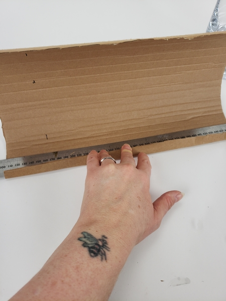 Use a steel ruler to fold an edge on the one side of the cardboard