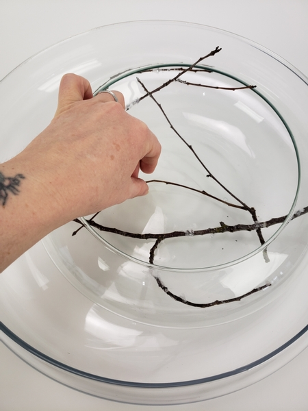 Create a dry twig design inside the vase