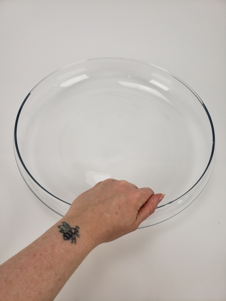 Place a large glass container on a flat surface