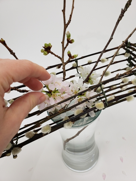 Place a few blossoming stems into the basket