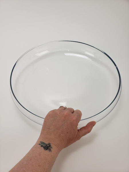 Place a shallow round container on your working surface